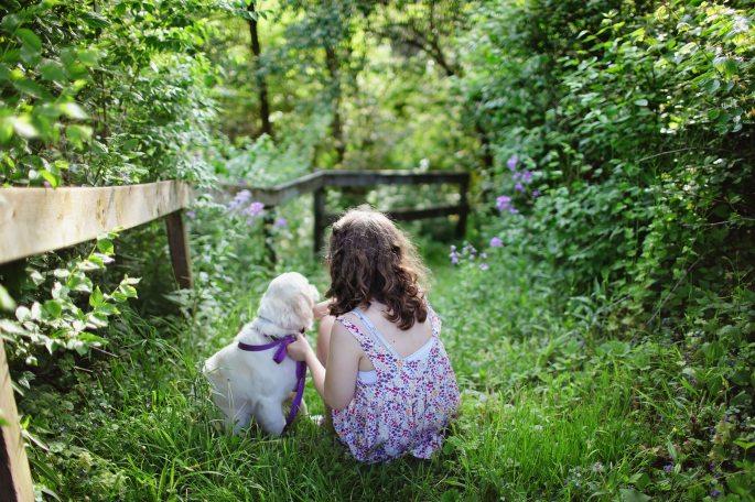 child and puppy wiht flowers